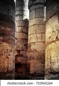 Ancient columns with stone reliefs and egyptian hieroglyphs for your architectural background. Karnak Temple Complex in Egypt - colonnade of of the Great Hypostyle Hall.