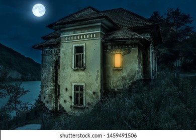 Ancient creepy house with spooky deails in the moonlight with dark horror atmosphere. Haunted house scene like in Halloween movies. Old frightful abandoned manor with full moon in the ghost tour