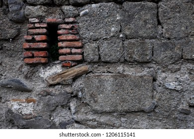 Ancient dark wall of gray stones, red loopholes of red brick, chaotic masonry. background