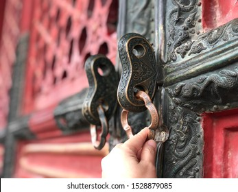 Ancient door with keys. A hand knocking on the door. Forbidden city, China. Selective focus.