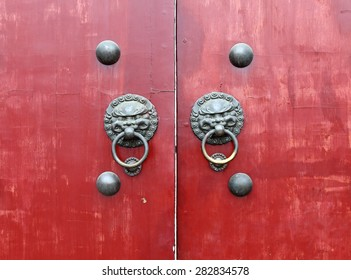 Ancient door knocker with the face of a mythological Chinese guardian creature known as Qilin on a brown wooden door.