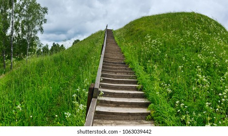 Ancient earth wad in Belozersk wooden staircase to climb a green hill.