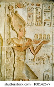 Ancient Egyptian bas relief carving of Pharaoh Ptolemy IV making an offering to the gods.  Temple of Deir el Medina, Luxor, Egypt. Ancient carving over 1000 years old.