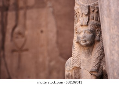 Ancient Egyptian goddess Isis and Ankh the ancient symbol of life, carved into an ancient temple wall in the background. Karnak, Luxor, Egypt
