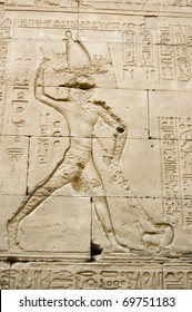 Ancient Egyptian hieroglyphic carving showing the Pharaoh king killing the god of the underworld - Seth - who has taken on the form of a hippopotamus. Outer wall of the Temple of Horus, Edfu, Egypt.