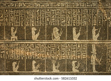 Ancient Egyptian hieroglyphs engraved on a old black stone
