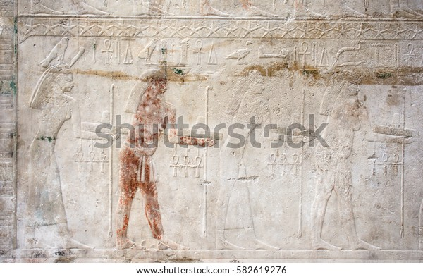 Ancient Egyptian illustrations engraved in a old stone