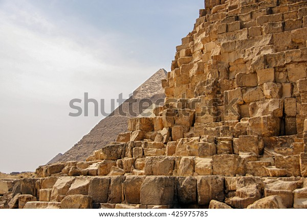 Ancient Egyptian pyramid of Giza against the sky and close up of the pyramid blocks