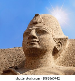 Ancient Egyptian sculpture in Cairo, Egypt, against blue sky with sun flare.