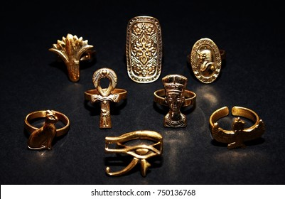 Ancient Egyptian styled trendy rings isolated on dark background.