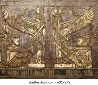 Ancient Egyptian wood relief carving of two winged women, gold gilded