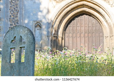 Ancient English church yard in Summer. Rural countryside cemetary with overgrown wildflowers and old concrete headstone.