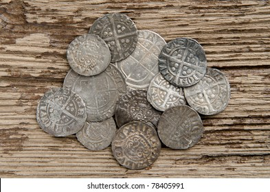 Ancient English silver coins on an oak table