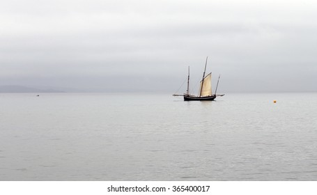 Ancient fishing boat, a Cornish lugger, becalmed off Newlyn, Cornwall, England, UK.
