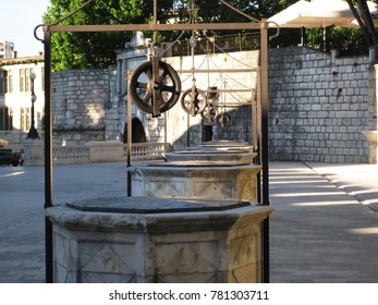 Ancient, five wells with steel coil of stone in the old town of Zadar during the summer