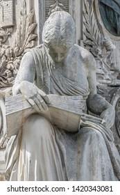 Ancient fountain statue of sensual Italian Renaissance Era woman reading a big book, Magdeburg, Germany, details, closeup