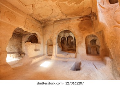 Ancient frescoes on the ruins of the stone walls of an antique church hollowed out of an old sandstone rock in the valley of Cappadocia, close-up view.