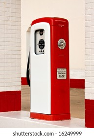 Ancient gas pump painted in bright white and red in the setting of an old gas station
