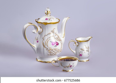 Ancient German faience tea (coffee) service with a kettle, a milk cup and a cup filled with tea (coffee) on a gray-gray background