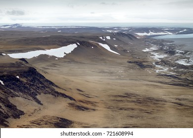 Ancient glacial trough. Regional ablation zone of modern shrinking glacier, moraine boundary (lateral moraine), rotted rocks. Novaya Zemlya Archipelago. North Island. Photo from helicopter