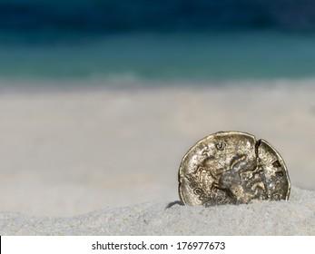 Ancient gold coin on white sand beach, closeup