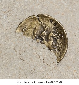 Ancient gold coin on white sand, closeup