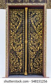 Ancient golden carving wooden door of Thai temple. Thailand