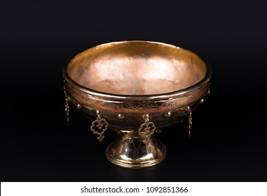 ancient golden cup on a black isolated background