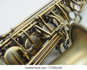 Ancient golden saxophone close up on white background