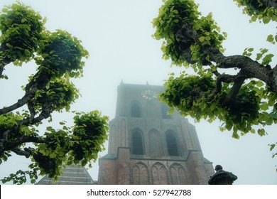 An ancient gothic church tower shrouded in mist, dating medieval times. Pollard willows are standing in front of the tower.  Their branches look like arms.