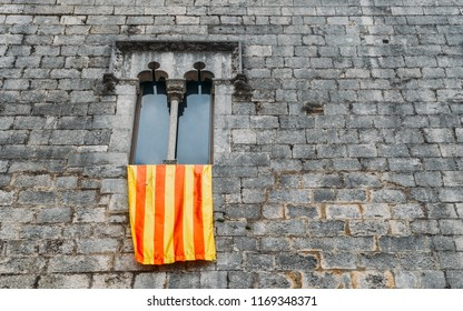 Ancient gothic window facade with a waving flag of Catalonia Catalunya known as Senyera, captured in Girona, Spain. The region's government wishes to separate from Spain