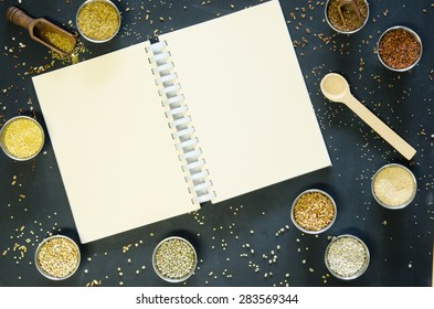 Ancient grains and gluten free alternatives on a black board surface with a coil bound book for your text