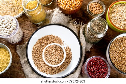 Ancient grains, seeds, beans on wooden background. Top view