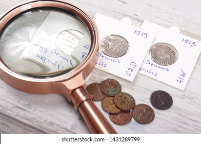 Ancient Grand Duchy of Lithuania coins and magnifying glass. Numismatics concept