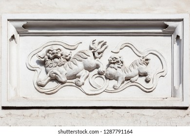 Ancient granite statue of mythological Chinese creatures Qilin on a old style brick and concrete wall,Fuzhou,Fujian,China