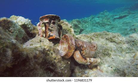 Ancient Greek Amphorae Relics On Rocky Seabed. Deep Blue Sea Horizon. Underwater Aegean Sea, Greece.