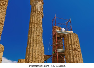 Ancient Greek Roman temple restoration scaffoldings. Unidentified worker on metal construction to support repair & preservation at Temple of Juno - Hera in Agrigento Sicily Italy archaeological site.