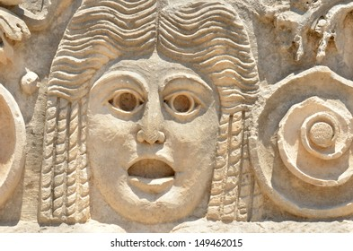 ancient greek sculpture of an actor's face showing an expression of shock or horror.