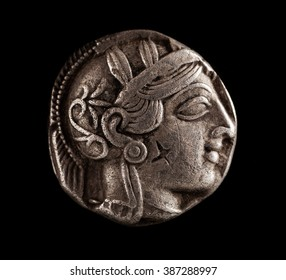 Ancient Greek silver coin on a black background, Athena, closeup, selective focus