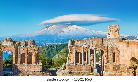 Ancient Greek theatre in Taormina on background of Etna Volcano, Italy. Taormina located in Metropolitan City of Messina, on east coast of island of Sicily.
