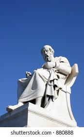 Ancient greek thinker on a postument on blue sky background.