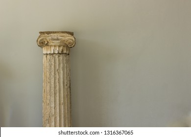 ancient Greek times marble antique column museum exhibit object photography on white wall background with shadows and empty copy space for your text or inscription