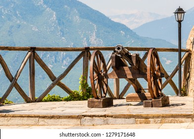 Ancient gun on wooden frame with wheels standing on terrace fenced with wooden logs railings, outdoor lantern and scenic Meteora mountains on the background