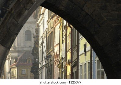 Ancient historical buildings seen through an arch way in Prague