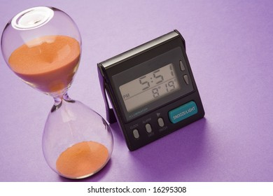 An ancient hour-glass-style egg-timer and a modern digital clock.
