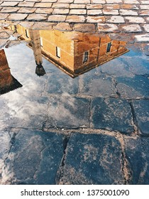 Ancient house reflection in the puddle