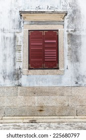 Ancient house with vintage window style on old white wall