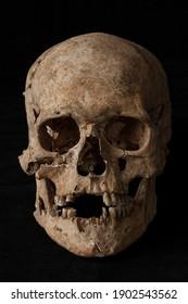 ancient human skull on black background