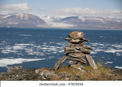 An ancient Inuit inukshuk serves as a landmark for seafarers in a fjord of Baffin Island, Nunavut, Canada.  This inukshuk is estimated to be at least one thousand years old.