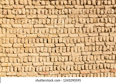Ancient islamic Arabic muslim old town house wall built of yellow brown mud bricks on sunny day background texture. Al Qasr, Dakhla Oasis, Western Desert, New Valley Governorate, Egypt, Africa.